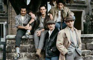 """L'éphémère groupe humoristique """"Les Cinq"""", en 1985, sur le tournage du film """"Le téléphone sonne toujours deux fois !!"""" de Jean-Pierre Vergne, avec les futurs """"Inconnus"""" Didier Bourdon (debout, à droite), Bernard Campan (au milieu, sur le mur) et Pascal Légitimus (à gauche, sur le mur), Smaïn (à droite sur le mur) t Seymour Brussel (debout, à gauche)."""
