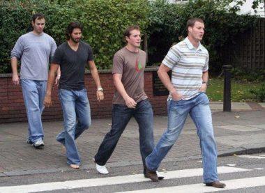 Quatre jeunes gens traversant un passage piétion en file indienne