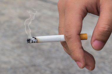 Main tenant une cigarette allumée