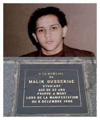 Photographie et plaque commérorative à la mémoire de l'étudiant français Malik Oussekine, battu à mort par des policiers du PVM (Peloton des Voltigeurs Motocyclistes) de la préfecture de police, devant le 20 de la rue Monsieur-le-Prince, à Paris (75)