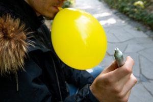 Un jeune inhalant du protoxyde d'azote à l'aide d'un ballon de baudruche préalablement gonflé à l'aide d'une cartouche de gaz pour siphon