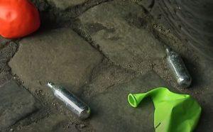 Cartouches de protoxyde d'azote et ballons de baudruche jetés sur un trottoir après usage