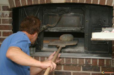 """""""Avoir du pain sur la planche"""" : enfournement d'un pain dans un fournil sur une """"pelle à fournil"""""""