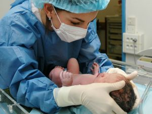 Une sage-femme examinant un nouveau-né