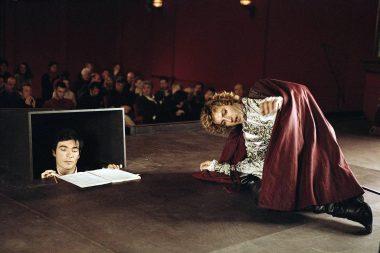 Un souffleur, dissimulé aux yeux du public, prêt à aider un comédien, sur scène, en train de jouer