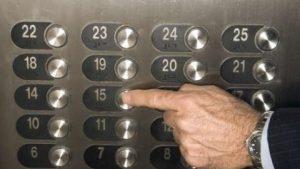 Un index masculin appuyant sur le bouton du 15e étage, dans un ascenseur