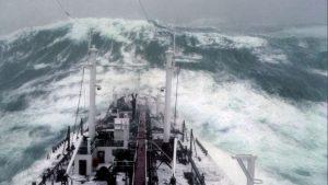 """Un navire en pleine tempête, sur le point d'embarquer une """"baleine"""", c'est à dire, dans le jargon maritime : une énorme lame ou vague"""