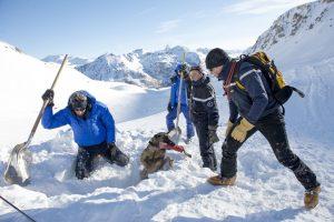 Une équipe de secouristes effectuant un dégagement de victime d'avalanche, en montagne