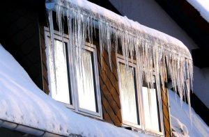 """Des stalactites de glace (ou """"pagothèmes"""" )sur la façade d'une maison"""