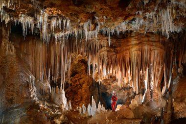 Des stalactites au plafond d'une grotte et des stalagmites sur le sol