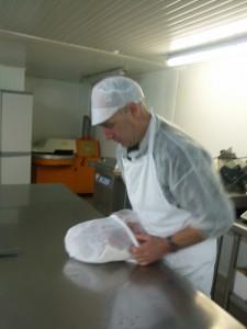 """Un charchutier en train d'emmailloter un jambon dans sa """"Chaussette à jambon"""", également appelée """"Sac mousse"""" ou """"Torchon"""""""