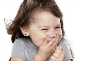 Une toute petite fille en train de pouffer de rire