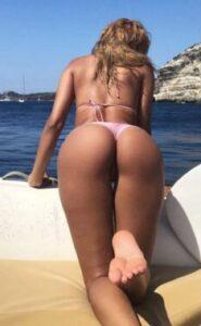 Une fille croustillante, penchée sur le bastingage d'un bateau