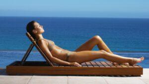 Une femme bronzant sur un bain de soleil en teck