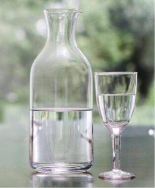 Une carafe d'eau et un verre à moitié pleins, sur une table, en extérieur