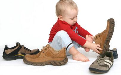 Un bébé essayant des chaussures d'homme