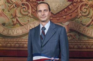 """Jacques Chirac, ceint de son écharpe demaire de Paris, devant la devise de la capitale : """"Fluctuat nec mergitur"""""""