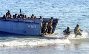 Des soldats jaillissant d'une péniche de débarquement, sur une plage