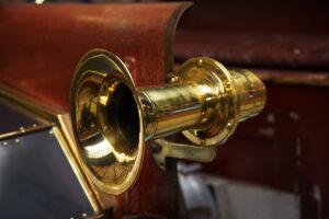 Un avertisseur sonore à air en forme de trompette, sur une automobile ancienne
