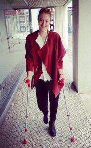 Une jeune femme, marchant avec des cannes anglaises