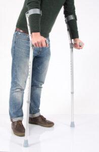 Un homme, debout, tenant des cannes anglaises avec coudières