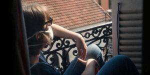 Une personne masquée, accoudée à une rembarde et assise sur un rebord de fenêtre