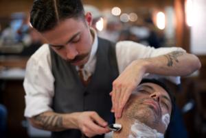 """Un barbier, utilisant un """"coupe-chou"""" ou rasoir à main"""