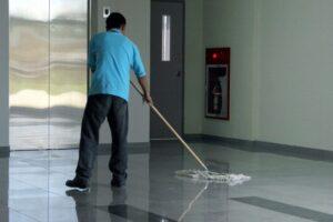 Un concierge ou gardien d'immeuble actuel, nettoyant l'entrée