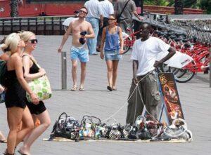 Un vendeur à la sauvette, prêt à s'enfuir en cas de contrôle avec ses sacs à main de marque de contrefaçon