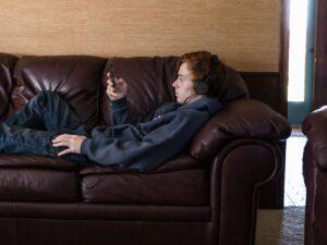 Un adolescent, allongé sur un canapé en cuir, écoutant son téléphone portable