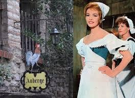 """Angélique (Michelle Mercier), dans le film """"Merveilleuse Angélique"""" (1965), devant l'enseigne du """"Coq hardi"""", qu'elle reprend et rebaptise """"Le Masque rouge"""", faisant prospérer cette modeste auberge parisienne, qui devient vite un endroit chic et réputé."""
