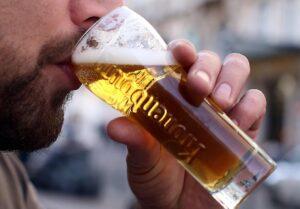 Un homme en gros plan, buvant de la bière